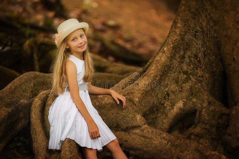 Pretty cute little girl posing with her lovely tree in the green summer garden. royalty free stock images