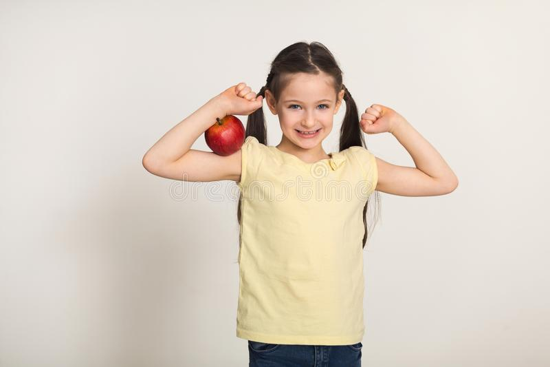 Pretty cute little girl with red apple over white background royalty free stock photography