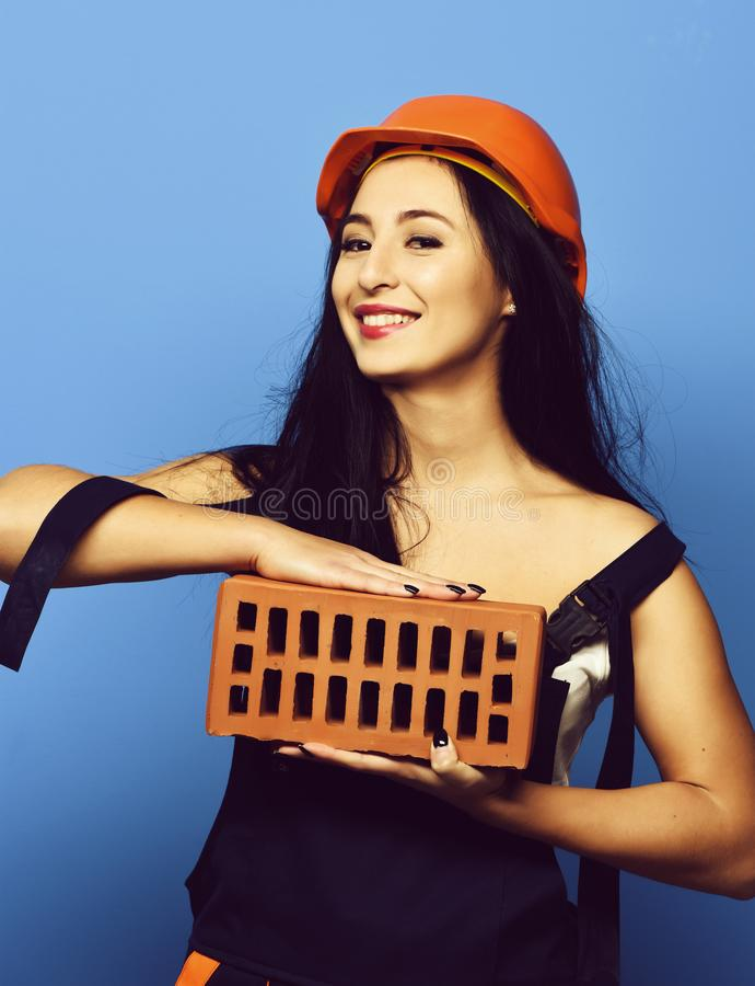 Pretty cute sexy builder girl or smiling brunette woman in uniform royalty free stock photography