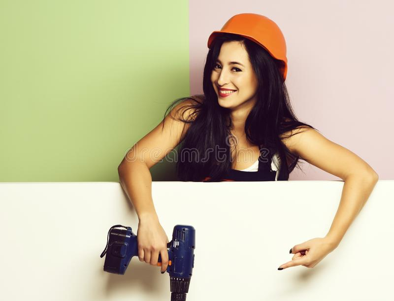 Pretty cute sexy builder girl or smiling brunette woman in uniform stock image