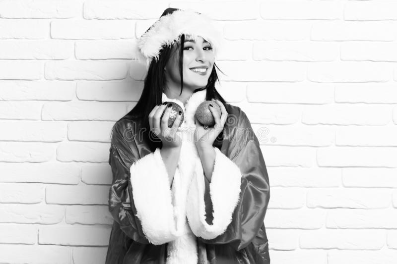 Pretty cute sexy santa girl or smiling brunette woman in new year sweater and hat holds christmas or xmas colorful balls stock photos