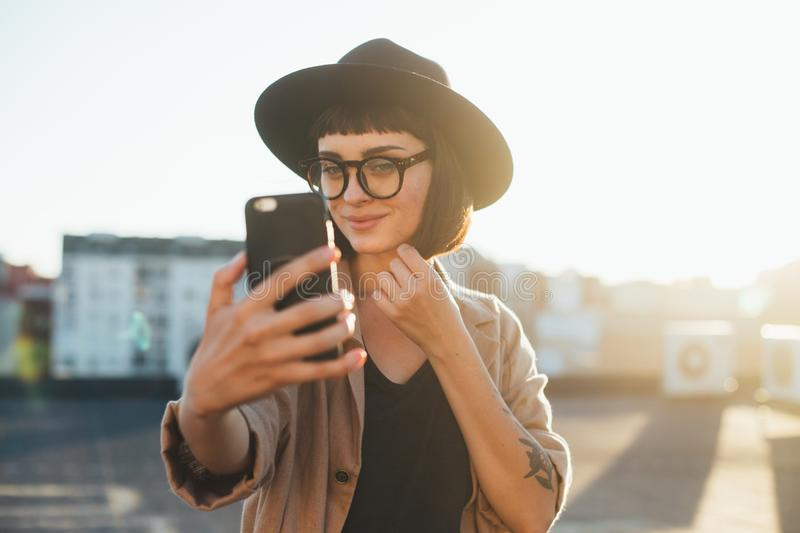 Pretty cute woman makes selfie sunset. Beautiful and attractive fashion model student or young teenager poses to make selfie photograph on smartphone for social royalty free stock image