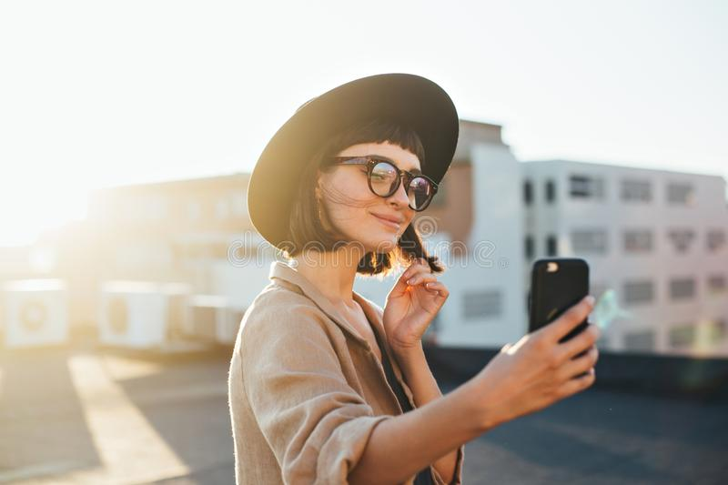Pretty cute woman makes selfie sunset. Beautiful and attractive fashion model student or young teenager poses to make selfie photograph on smartphone for social stock image