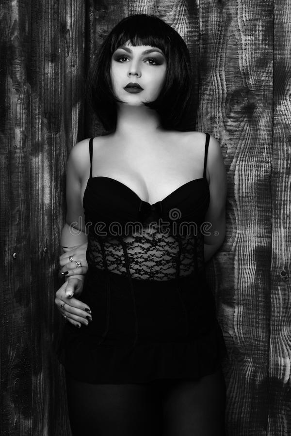 Pretty cute young stylish brunette woman in lace corset or underwear on plump body in black wig with red lips royalty free stock photo