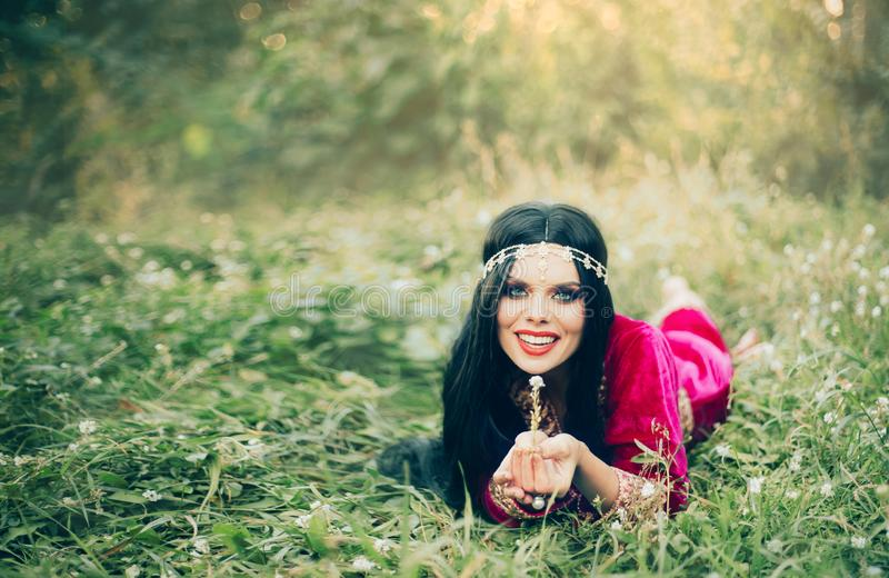 Pretty dark-haired woman lying on grass, tale of Roksolana, attractive fortune-teller with long black hair enjoying stock photography