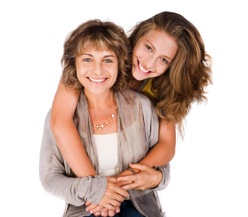 Pretty daughter hugging her mom from back. Young pretty daughter hugging her mum from back, indoors stock photo