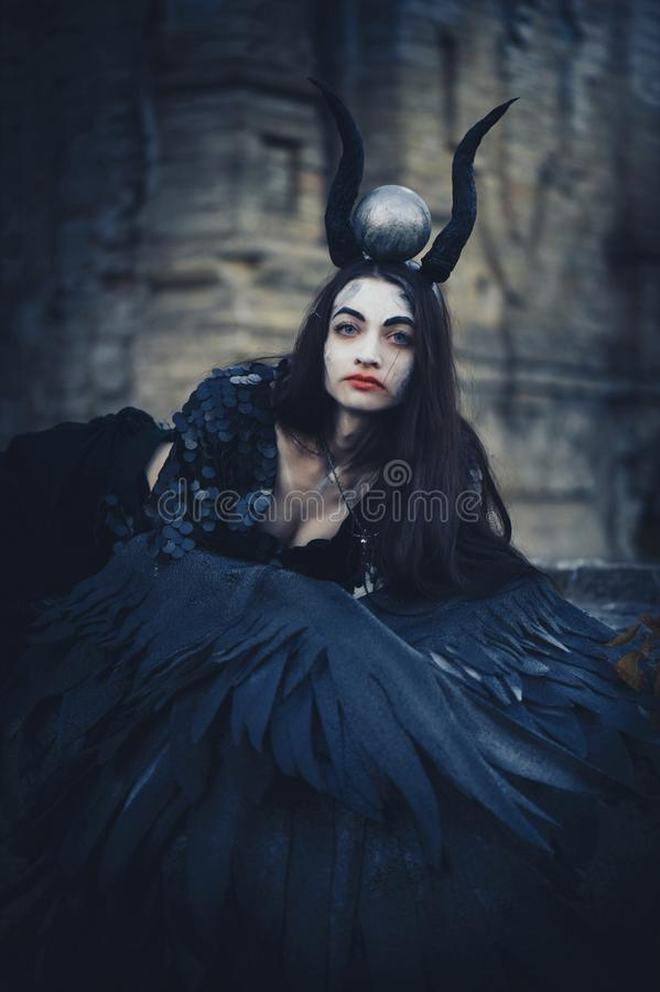 Pretty demon girl with black wings behind her back, goddess of another world beyond, Halloween black angel.  stock photos