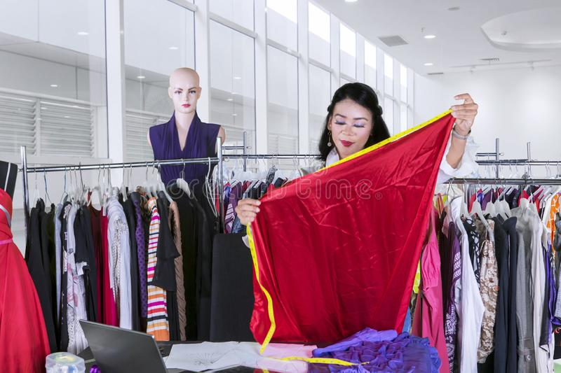 Pretty designer measuring a fabric in the workplace stock image