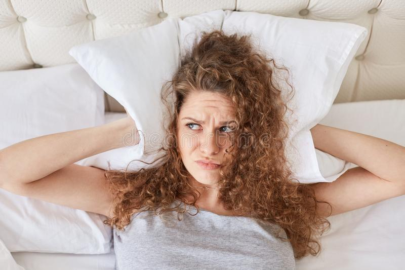 Pretty discontent female with curly covers ears with pillow, lies in bed, has insomnia, cant fall asleep because of noise, has sle royalty free stock images