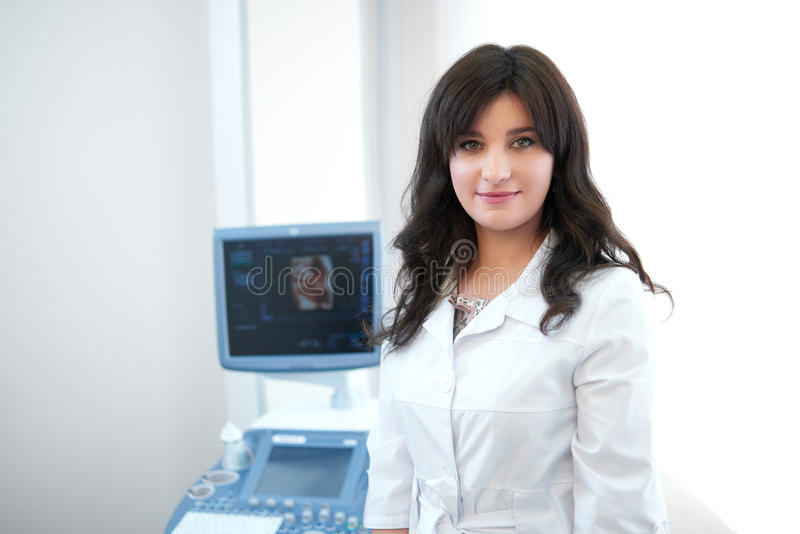 Pretty doctor against ultrasound equipment and computer. royalty free stock image