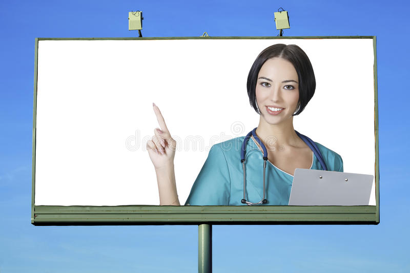 Pretty doctor smiling to you. From billboard with a space for your info royalty free stock photo