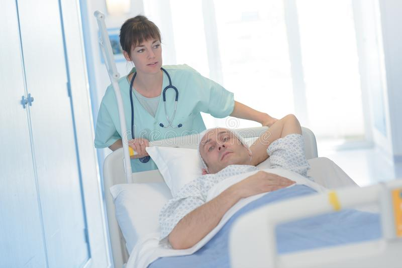 Pretty doctor transporting patient laying on stretcher stock photos