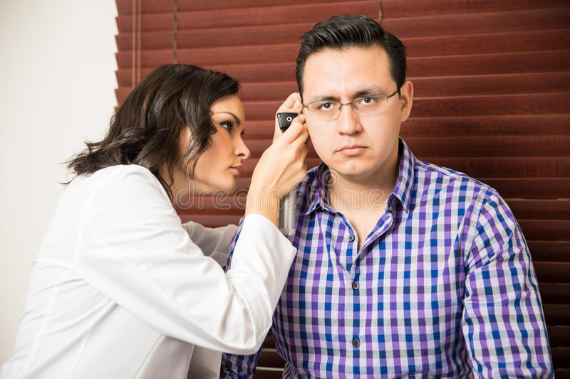 Pretty doctor using an otoscope royalty free stock photo