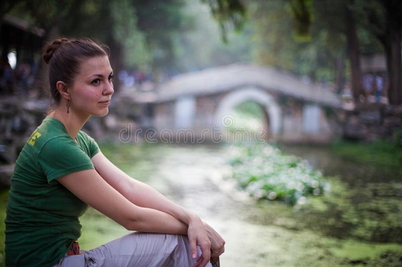 Pretty dreaming young woman sitting in summer park in shadow with blurred stone bridge on the background stock image