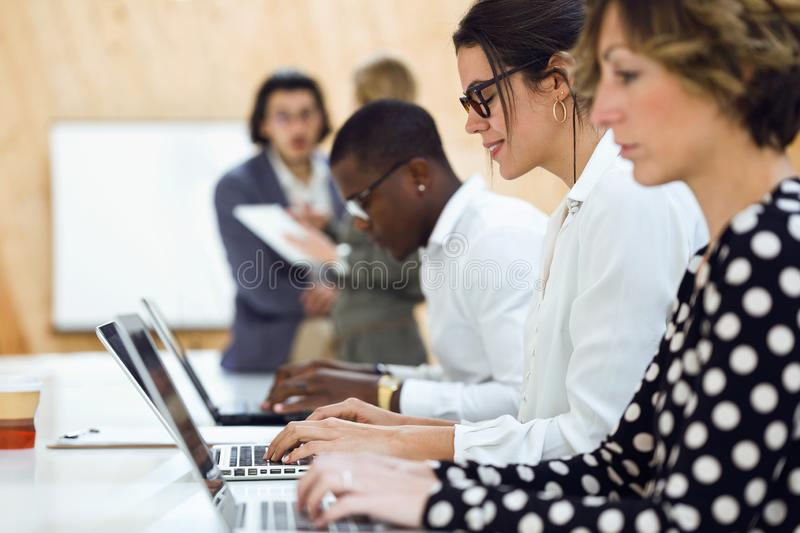 Pretty elegant businesswoman working with laptop in coworking place. Shot of pretty elegant businesswoman working with laptop in coworking place royalty free stock photography