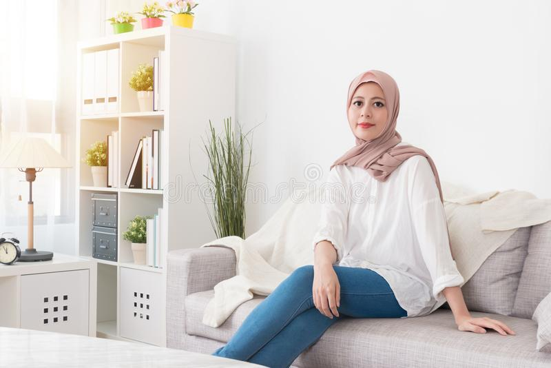 Pretty elegant muslim woman sitting on sofa couch royalty free stock photography