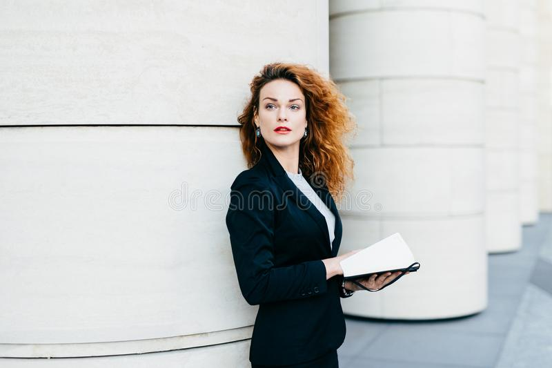 Pretty elegant woman with curly wavy hair dressed in black suit, holding pocket book in hands looking aside into distance, thinkin stock images