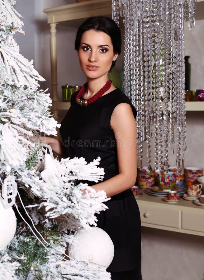 Pretty elegant woman decorating Christmas tree at home royalty free stock image