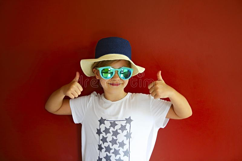 Pretty emothional child wear a hat and sunglasses on a red background royalty free stock image