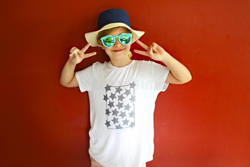 Pretty emothional child wear a hat and sunglasses on a red background stock photography