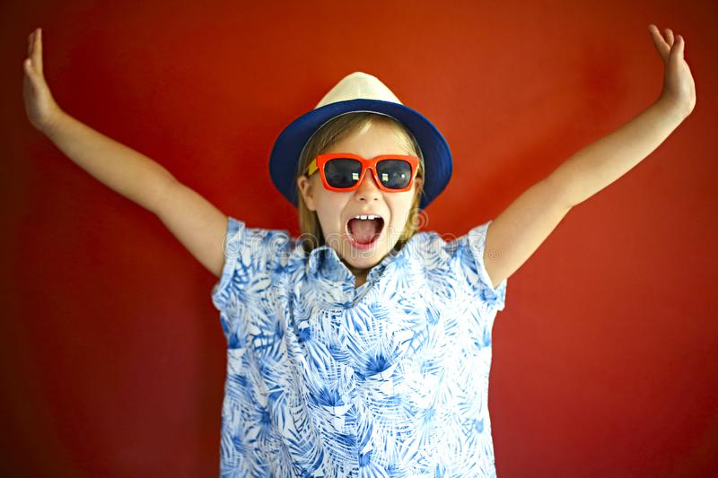 Pretty emothional child wear a hat and sunglasses on a red background stock photo