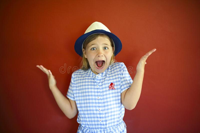 Pretty emothional children wear a hat on a red background. Copy space, daylight royalty free stock image