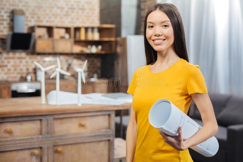 Pretty engineer feeling happy after finishing her work. Important scheme. Beautiful young experienced engineer smiling and holding a big drawing while feeling stock photography
