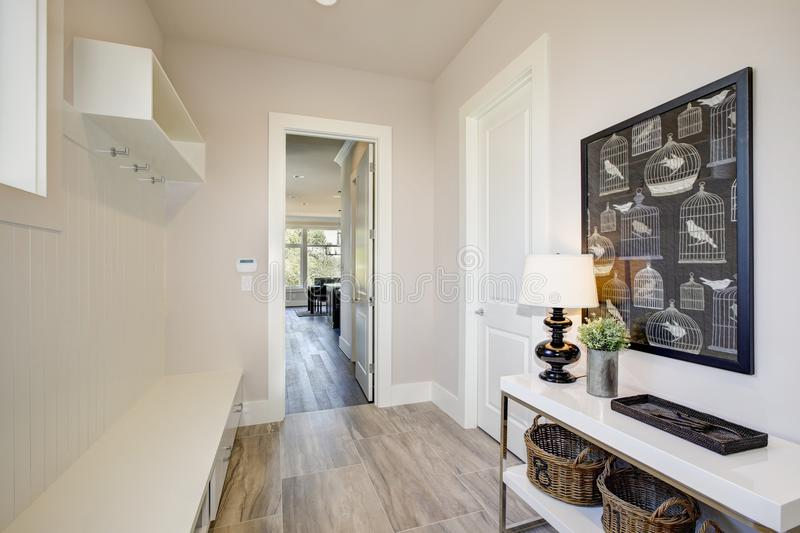 Pretty entrance foyer with an extra long built-in bench. Pretty entrance foyer with a wall clad in board and batten lined with an extra long built-in bench with royalty free stock images