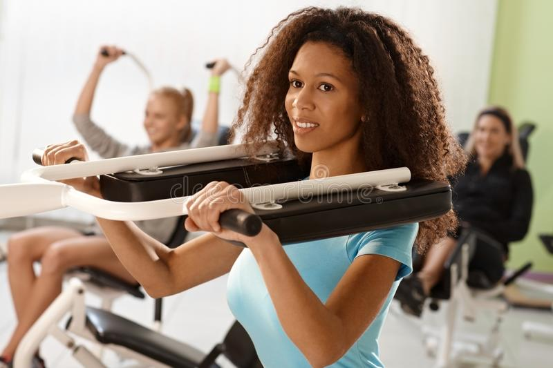 Download Pretty Ethnic Girl Exercising On Weight Machine Stock Photo - Image: 26681000