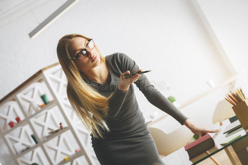Pretty european woman leaning on desk. Portrait of pretty european woman leaning on desk and pointing at something in office with items on shelf in the stock photography