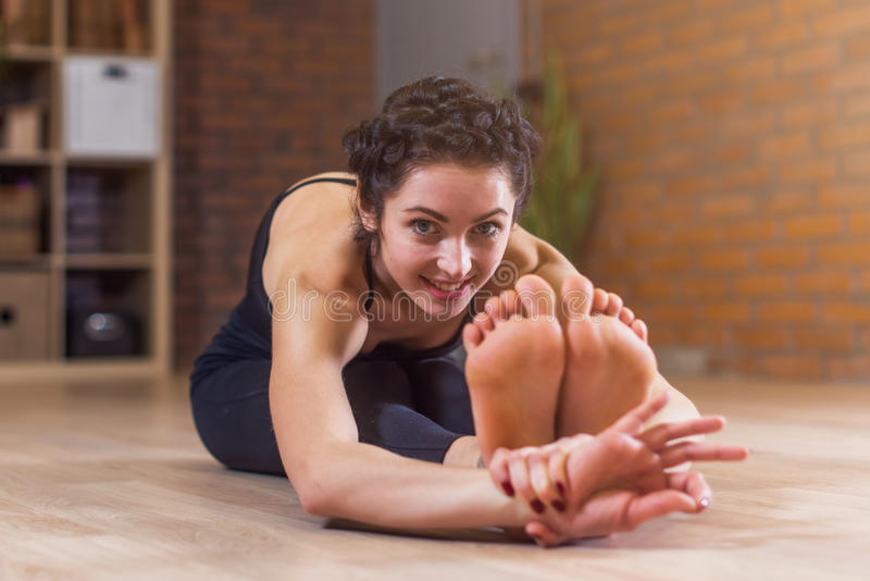 Pretty European woman sitting barefoot stretching her back and legs on floor bending forward looking at camera stock photography
