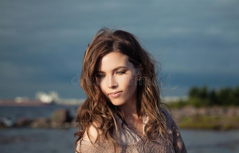 Pretty face. Beautiful model girl with long curly hair on ocean background, romantic beauty portrait royalty free stock image