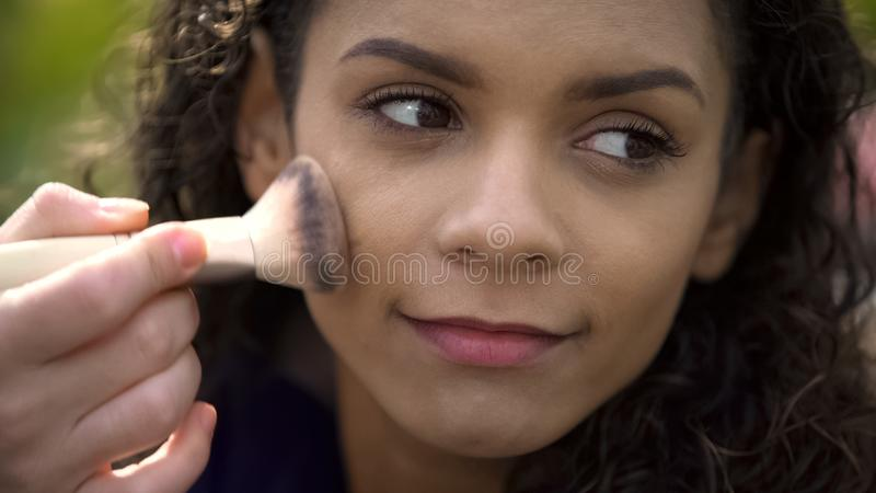 Pretty face of beautiful smiling female actress, make-up artist applying powder royalty free stock photo