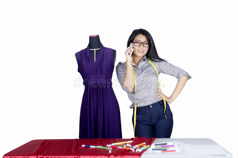 Pretty fashion designer talking on a smartphone royalty free stock photography