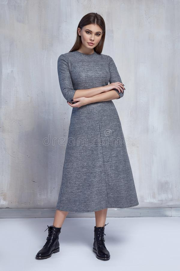 Pretty fashion woman wear wool grey dress casual trend clothes collection catalogue brunette hair party style model pose. Bright make-up beautiful face dress stock photography