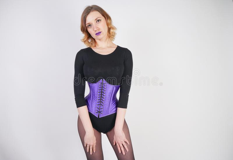 Pretty fashionable blonde girl wearing black jumpsuit with mesh pantyhose and purple corset on white background royalty free stock photos