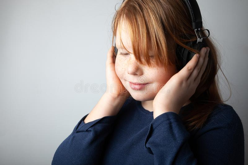 Pretty fat girl kid listens to music on headphones and gets pleasure.  stock images