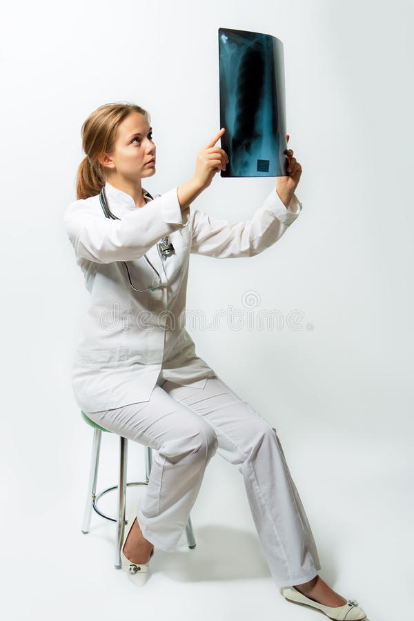 Pretty Female Blonde Doctor With X-ray Staring Stock Image