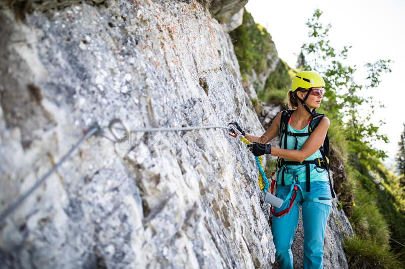 Pretty, female climber on a via ferrata royalty free stock photo