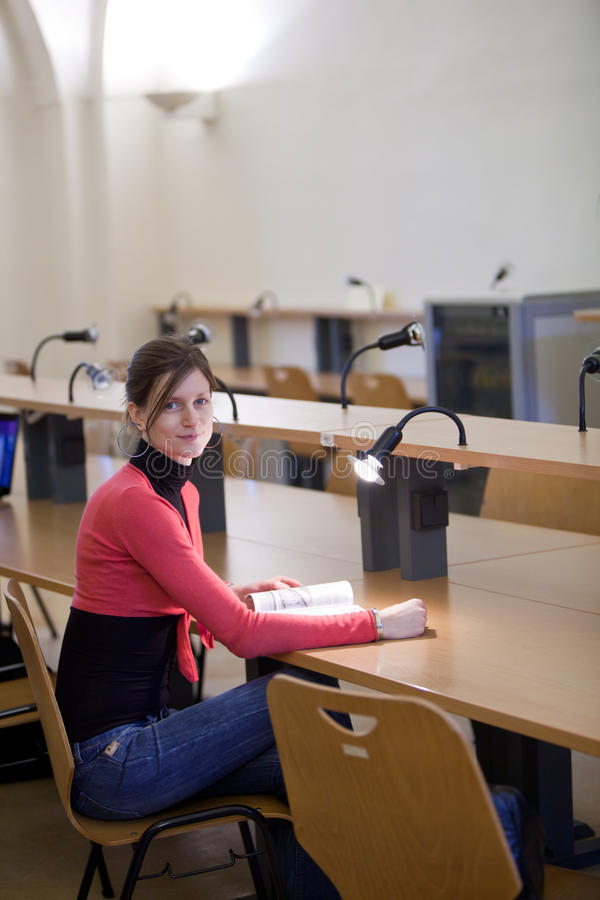 Pretty female college student in a library royalty free stock image