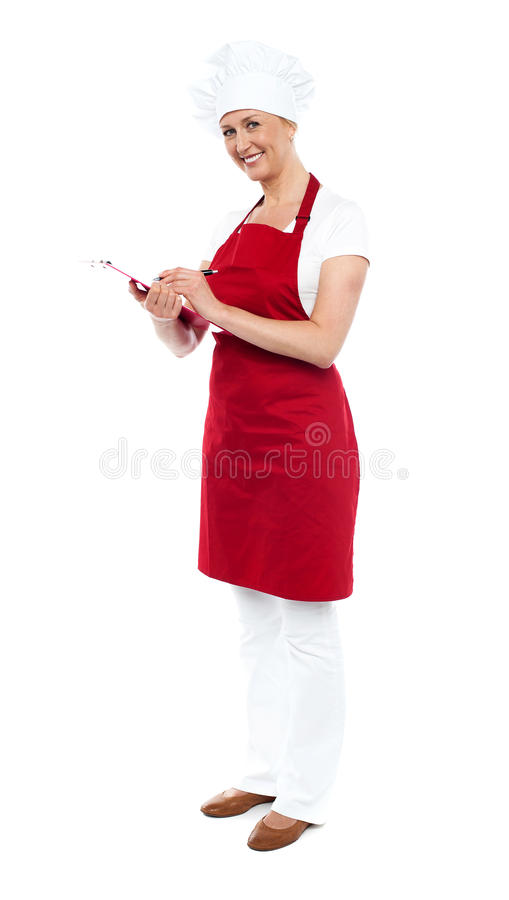 Download Pretty Female Cook Writing Recipe On Notepad Stock Photo - Image: 25997524