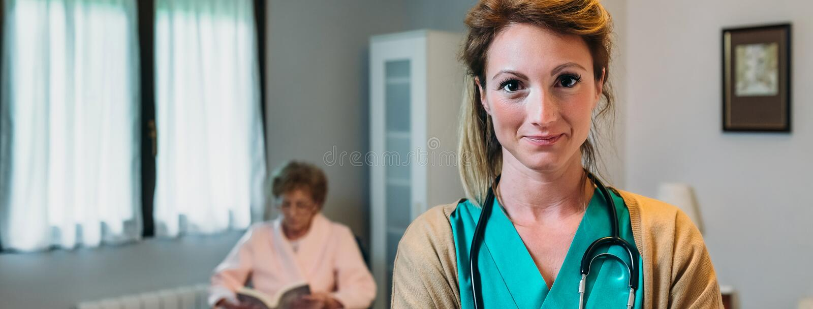 Pretty female doctor posing in a geriatric clinic. With elderly lady in a wheelchair stock photography