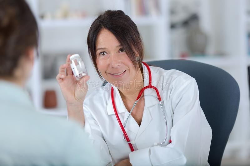 Pretty female doctor showing pills to patient stock image