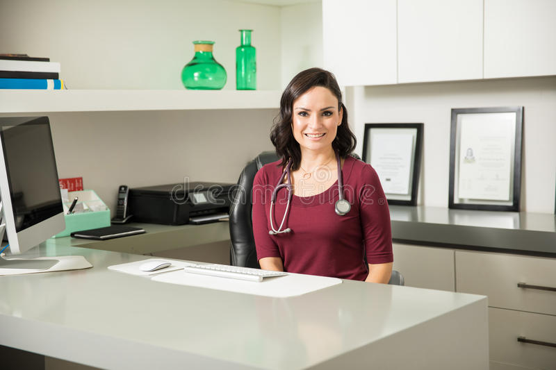 Download Pretty Female Doctor Sitting At Her Desk Stock Image - Image of lifestyle, practitioner: 83708281