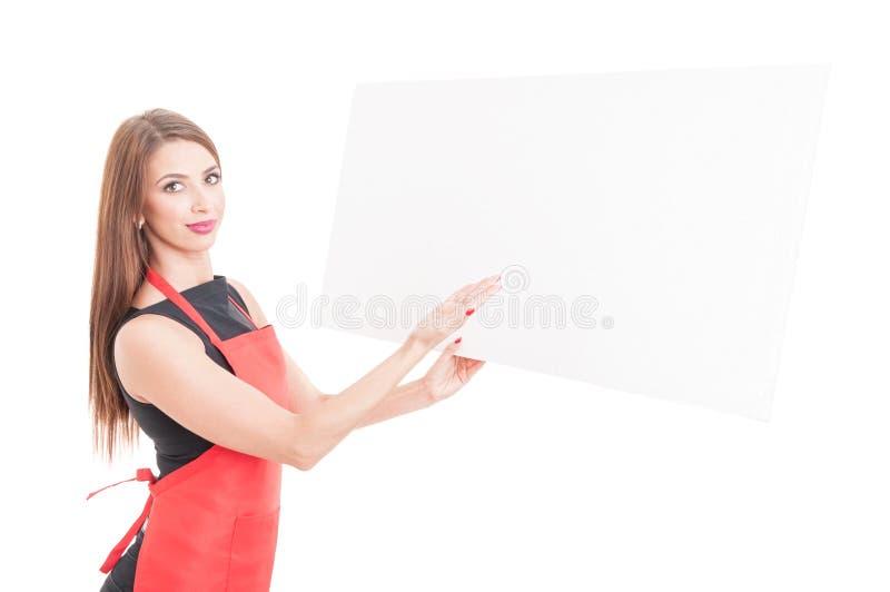 Pretty female employee presenting something on cardboard royalty free stock photos