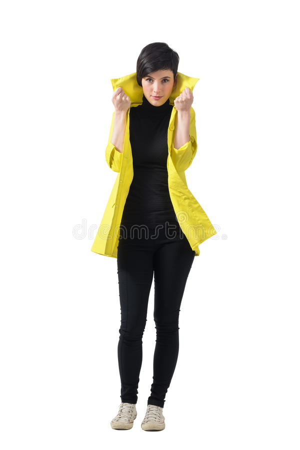 Pretty female fashion model in autumn clothes holding and pulling up coat collar. stock image