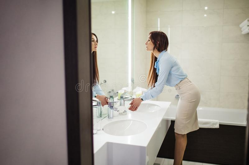Pretty female in formal wear looking at mirror while washing hands in bathroom. Image of pretty female dressed in romantic blue blouse, pencil skirt looking at royalty free stock photo