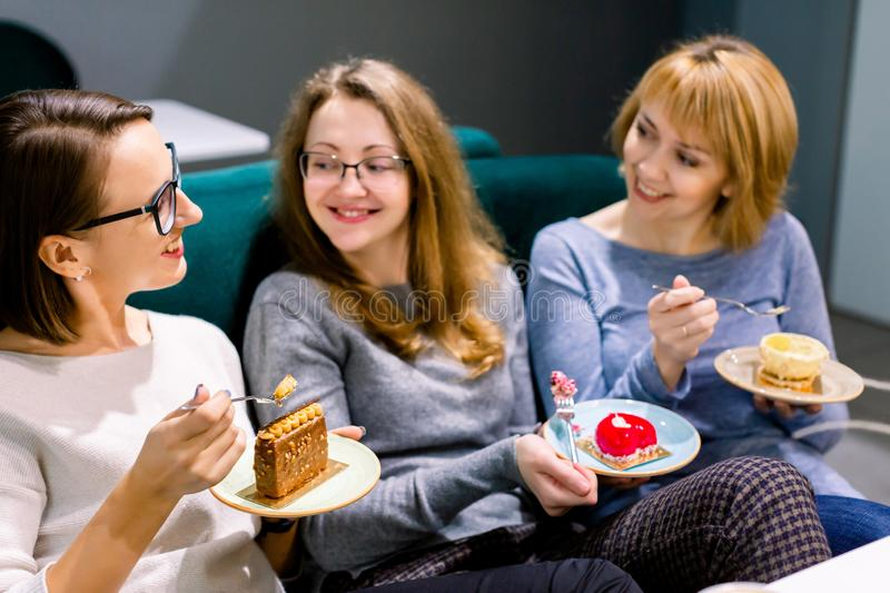 Pretty female friends eating tasty desserts cakes at indoor cafe, smiling happy. Best friends meeting.  royalty free stock photos