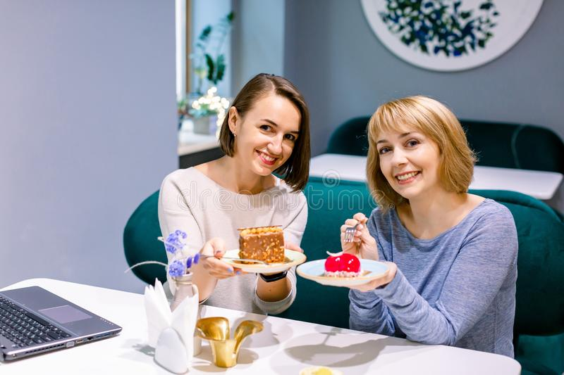 Pretty female friends sharing tasty colorful cakes at indoor cafe, smiling happy. Women friendship royalty free stock photo