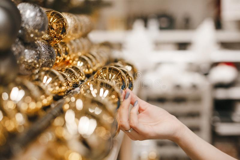Pretty female hand reaching and grabbing Christmas decoration, shopping woman hand with nude nails touching luxury gold. Christmas ball displayed in shop royalty free stock photography